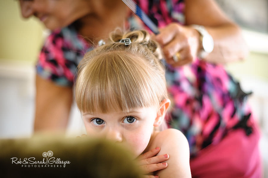 cute flower girl having hair styled before wedding