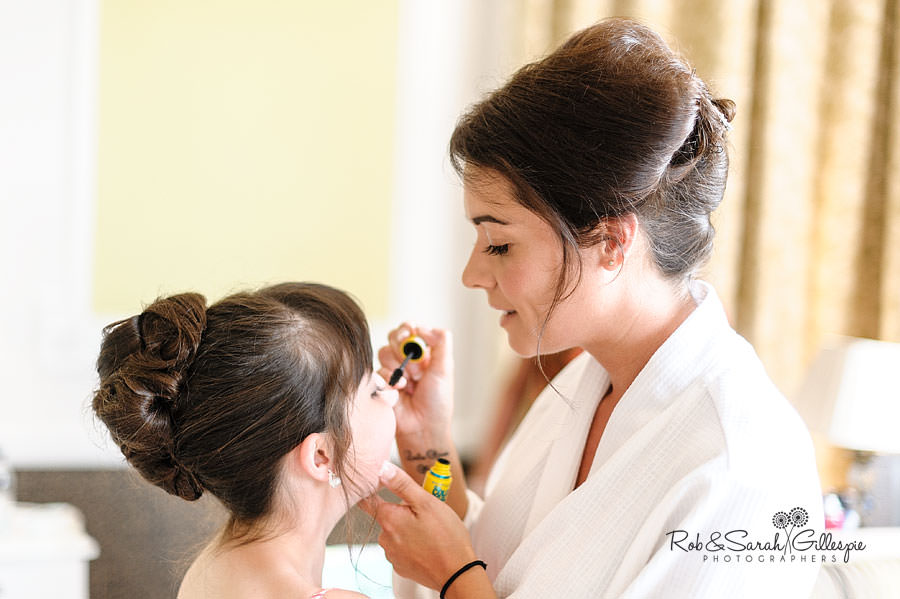 bride helping young bridesmaid with makeup before wedding