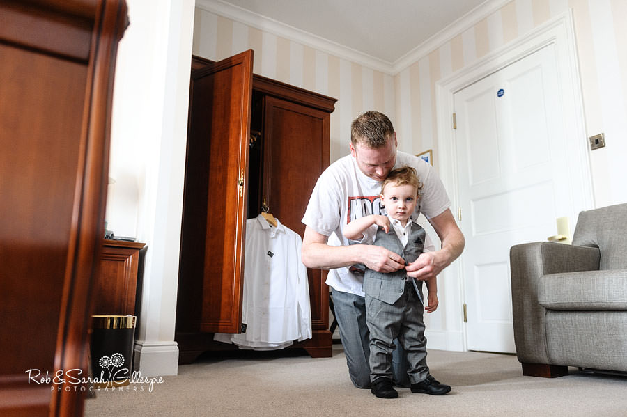 groom helping pageboy with outfit