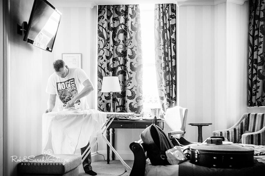 groom ironing shirt