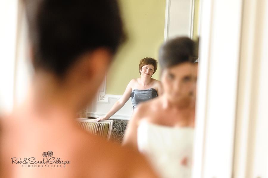 bridesmaid in mirror reflecting watching bride