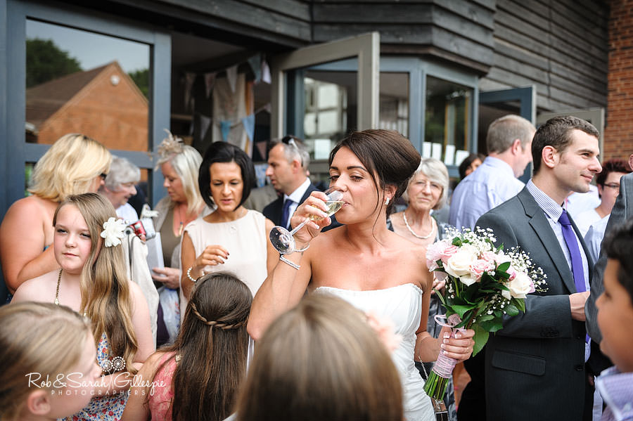 bride drinks champagne after wedding