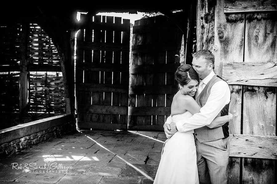 couple hug in front of beautiful old barn at avoncroft museum
