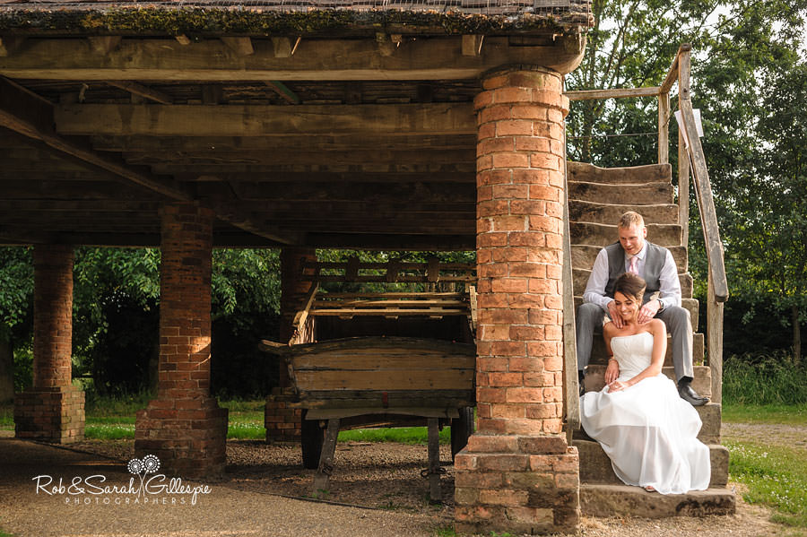 bride and groom sit on old brick building at avoncroft museum