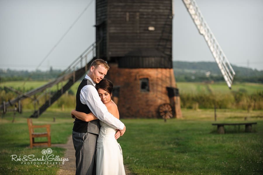 bride and groom in front of windmill at avoncroft museum
