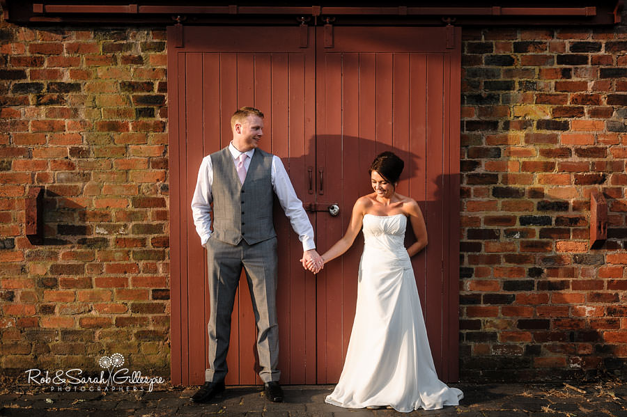 bride and groom hold hands in front of old building at avoncroft museum in evening light