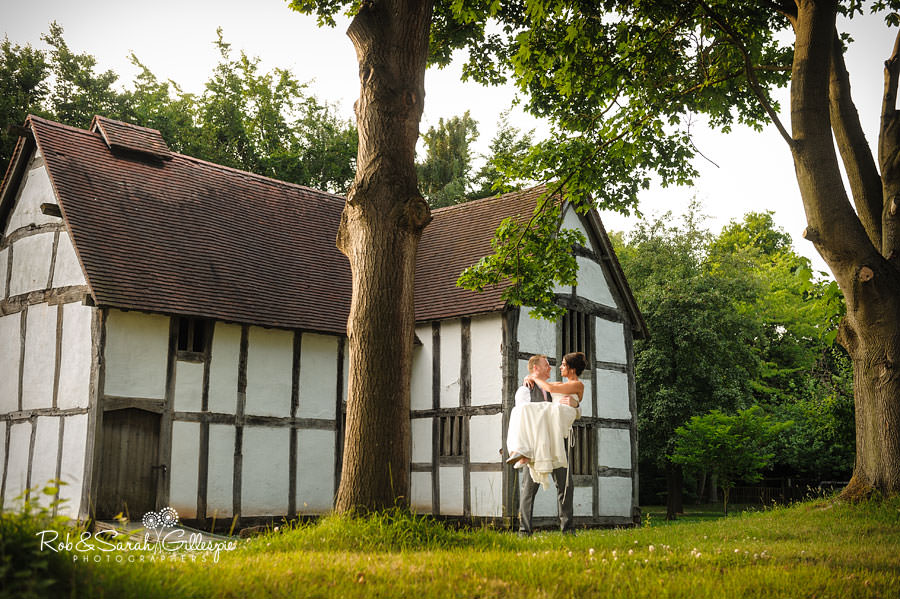 groom holds bride in front of old building at avoncroft museum