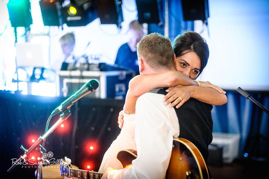 bride hugs husband during wedding reception