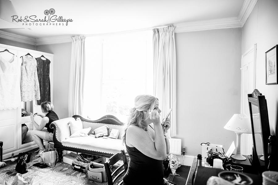reportage bride and bridesmaid applying makep