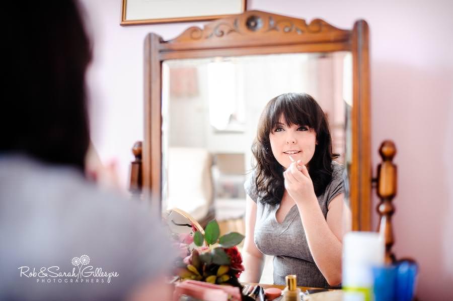bridesmaid applying lipstick in mirror