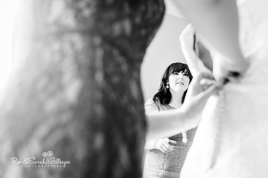 bridesmaid fastening brides wedding dress