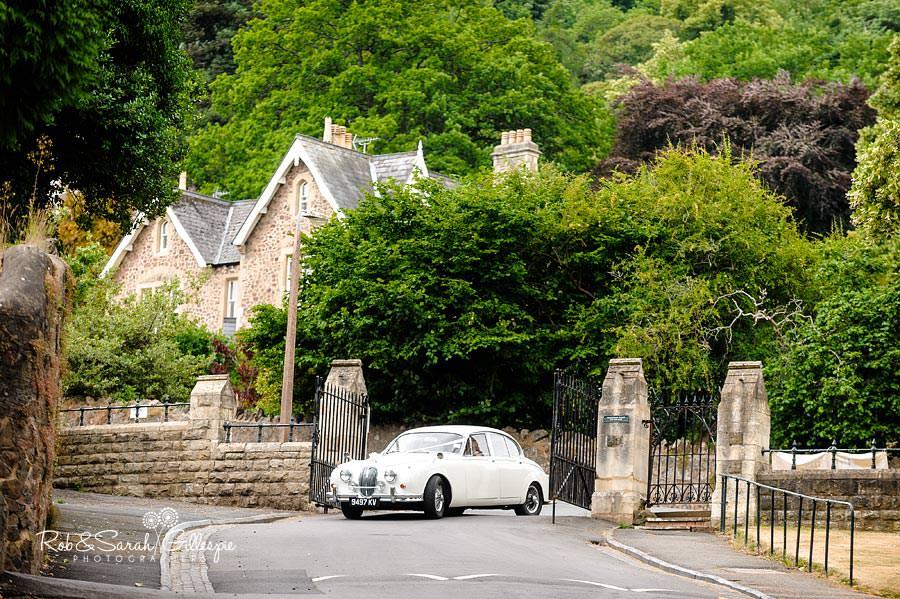 bride arrives in old jaguar