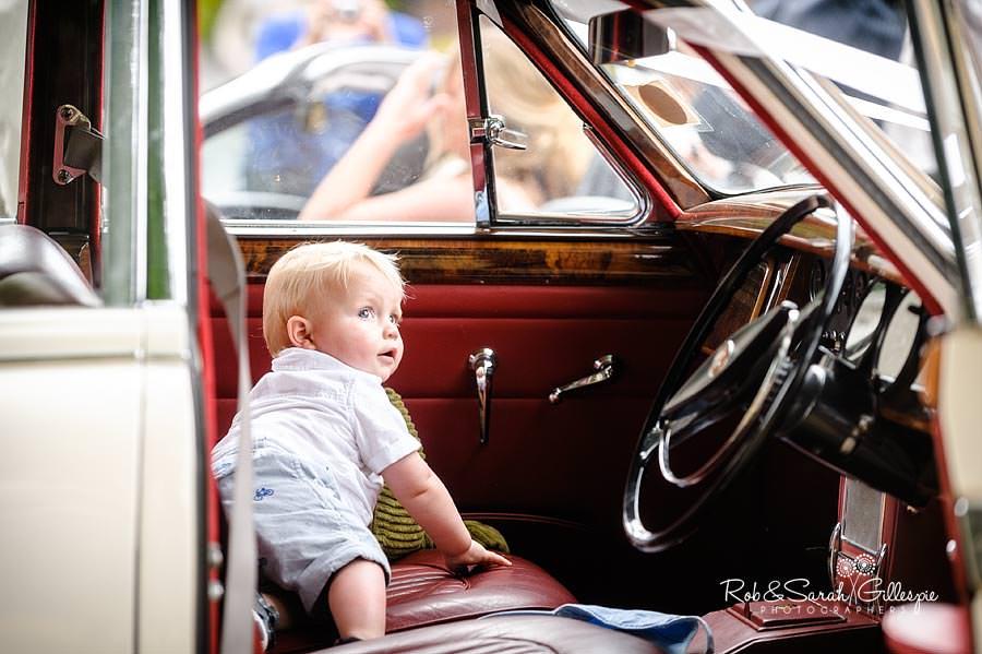 toddler plays in old jaguar car at wedding