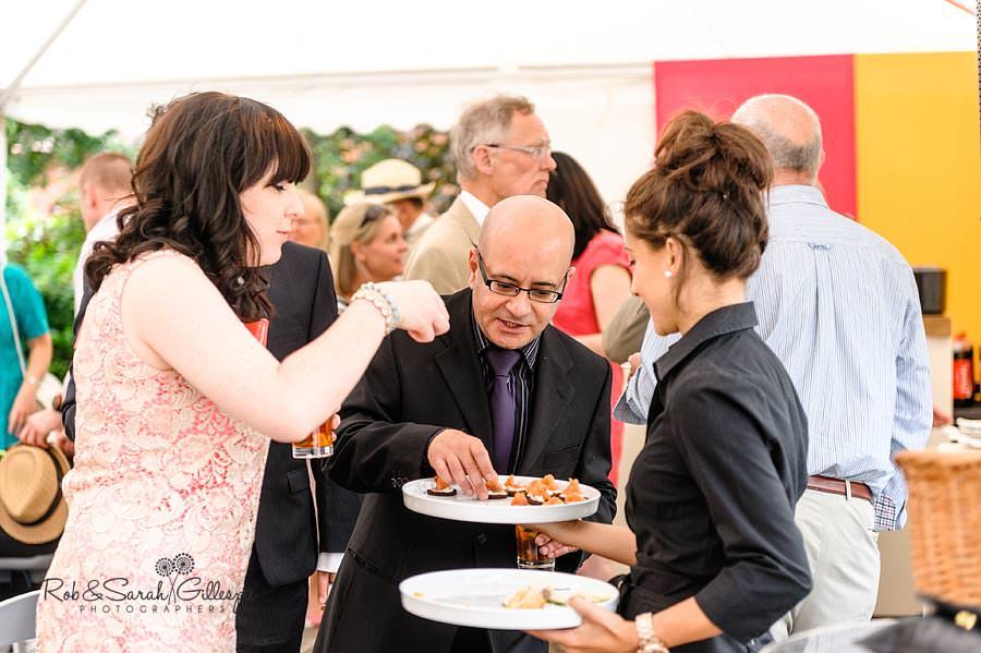 guests enjoying finger food at wedding reception