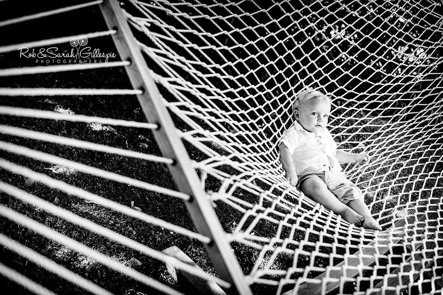 tolder in rope hammock at wedding reception