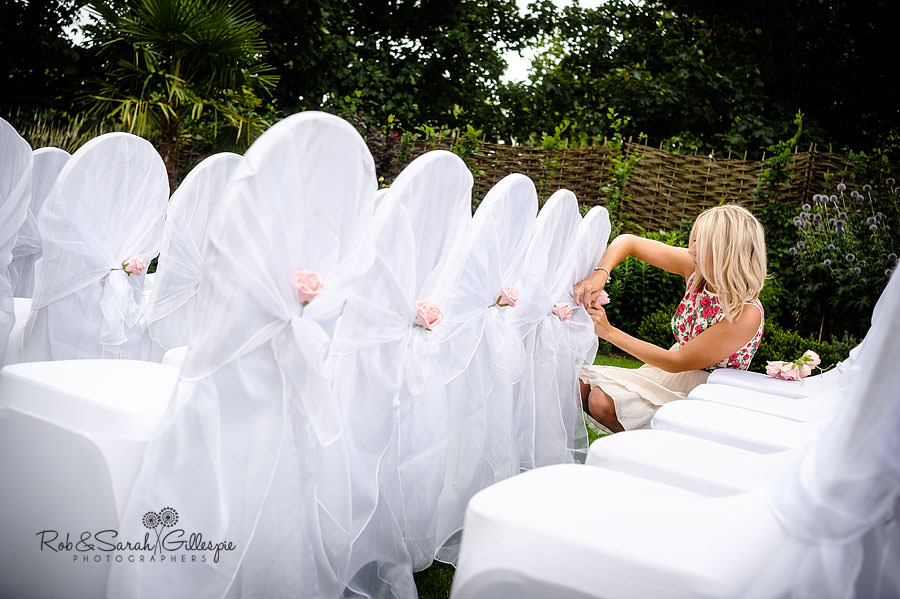 female wedding guest fixing chair covers