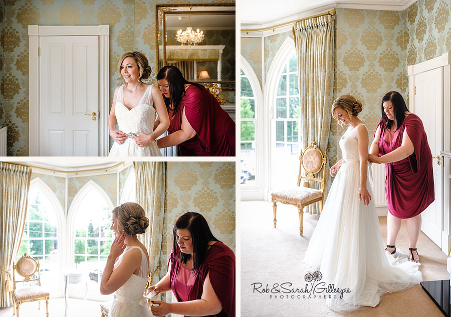 bride has wedding dress fastened at Warwick House