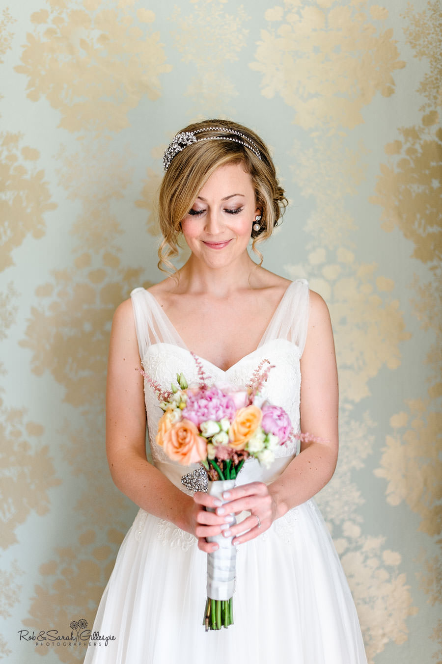 portrait of bride looking at bouquet in front of patterned wallpaper