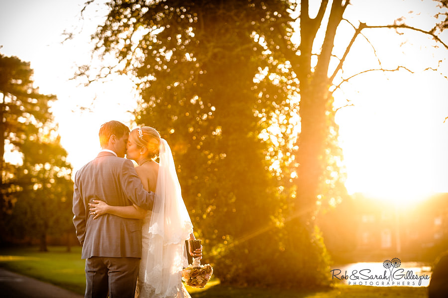 Bride and groom in Brockencote Hall grounds with beautiful light