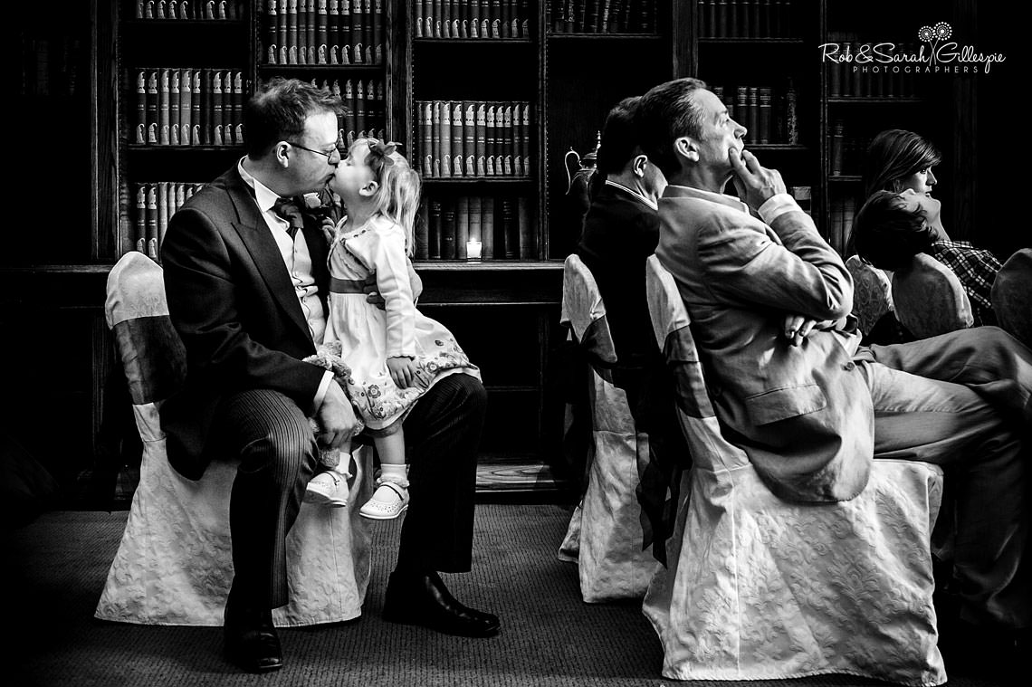 black and white photograph of young girl kissing her father during a wedding ceremony, with other guests waiting