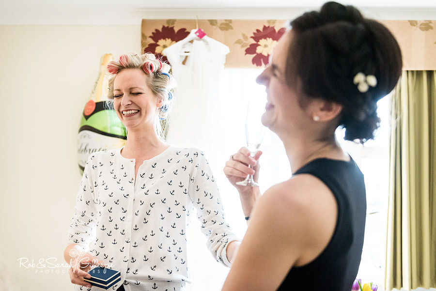 bride and bridesmaid sharing a joke before wedding