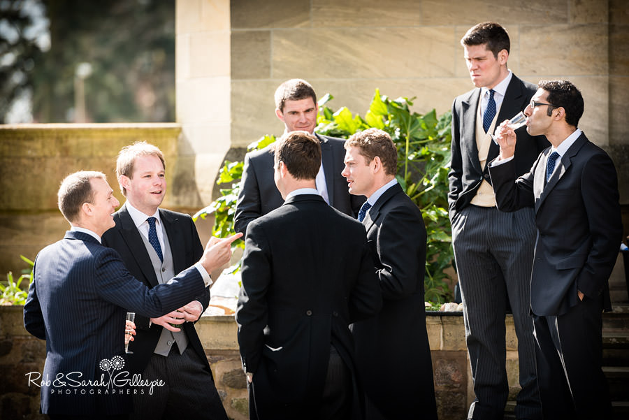 Groom and groomsmen chat and drink before wedding at Malvern College