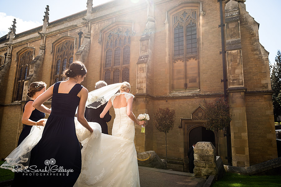 Dramatic photo of bride and bridsmaids walking to Malvern College Chapel for wedding ceremony