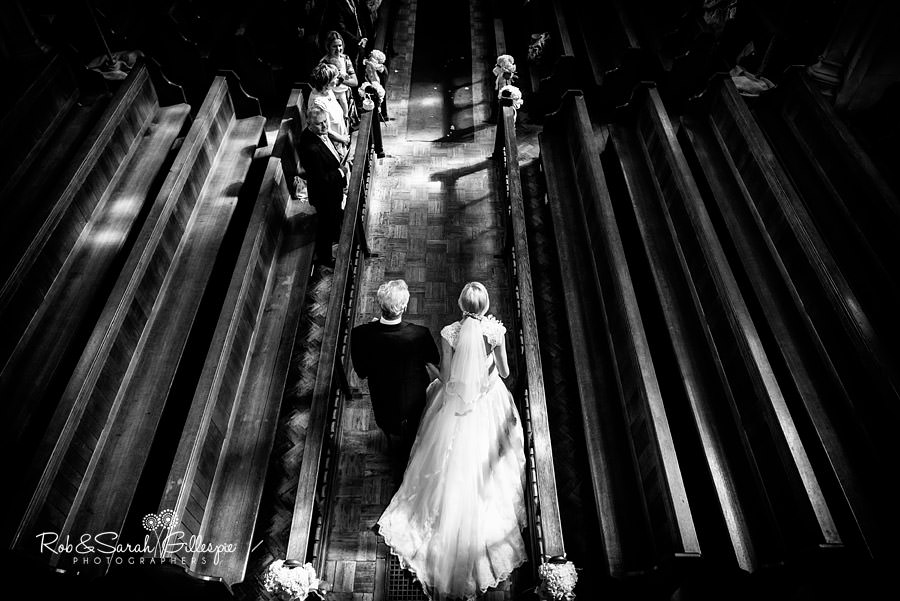 Dramatic black and white image of bride and father entering Malvern College Chapel