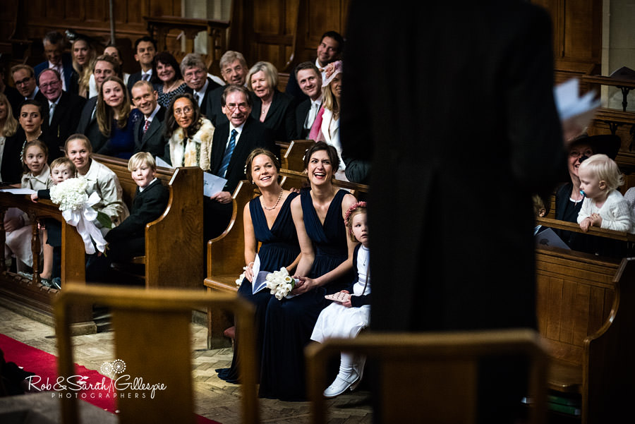 Bridesmaids and family laughing during wedding service
