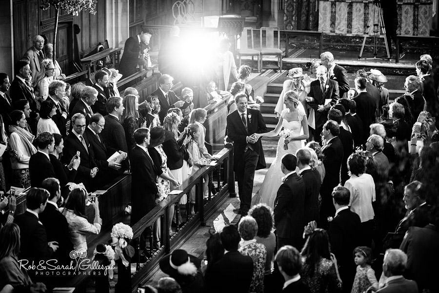 Bride and groom exit wedding at Malvern College Chapel as guest camera flash fires