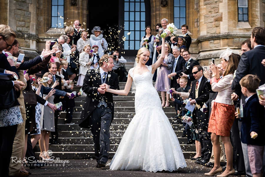 Bride and groom walk through confetti at Malvern College