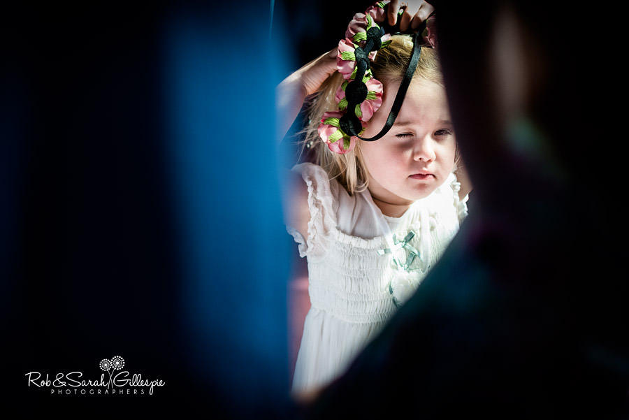 Little girl peers through wedding guests at wedding
