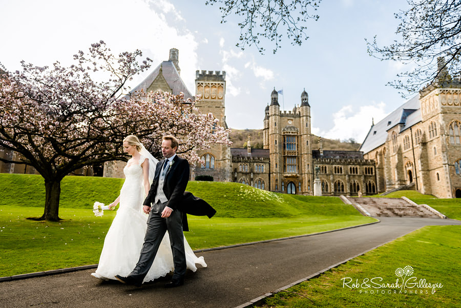 Bride and groom stroll through Malvern College grounds with blossom on trees in background