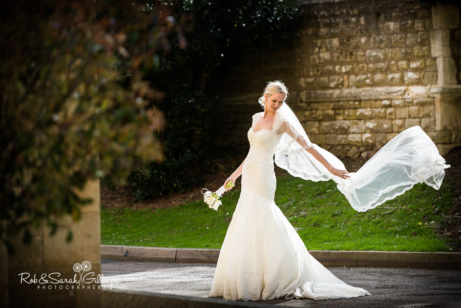 Bride lets veil flow in the breezr at Malvern College