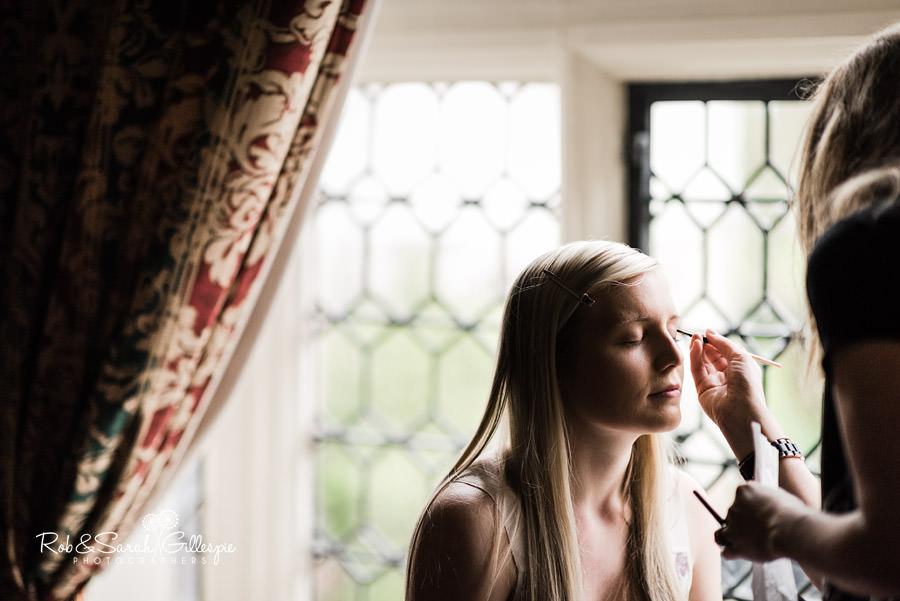 Bride having wedding makeup applied in window light