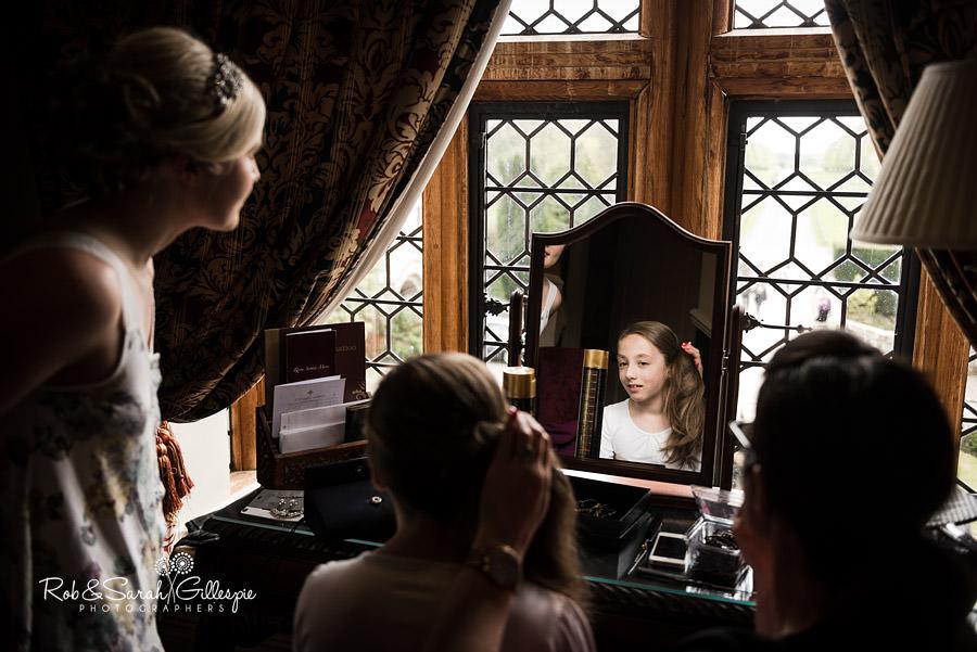 Bridesmaid looks in mirror before wedding