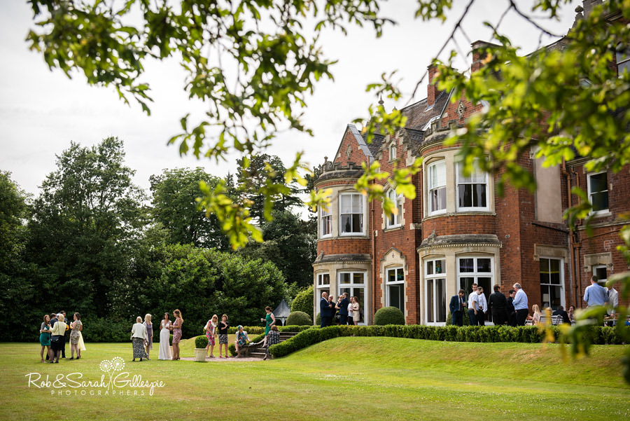 Wedding guests relax in sunshine at Pendrell Hall