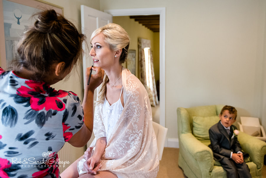 Bride having makeup applied at Delbury Hall while pageboy looks on