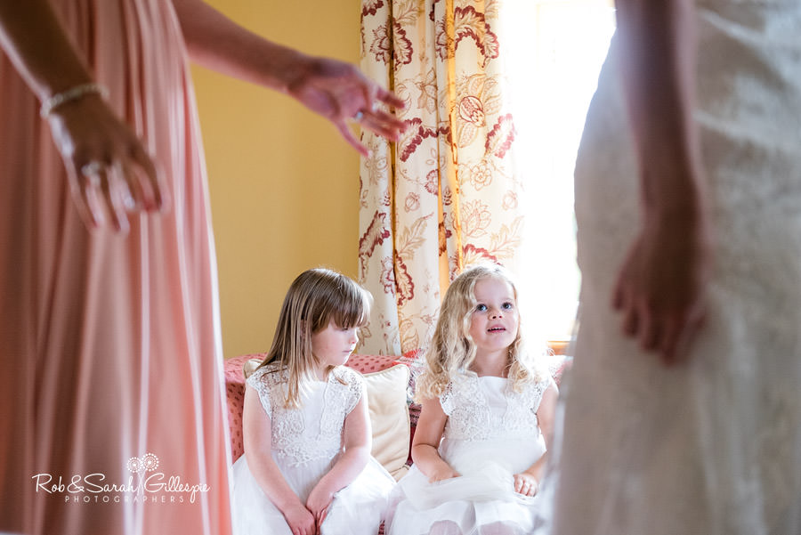 Flower girls look on as bride gets ready for wedding at Delbury Hall