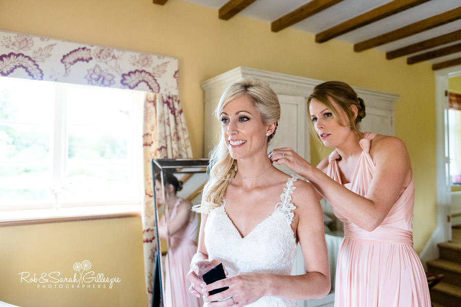 Bridesmaid helps bride with dress at Delbury Hall