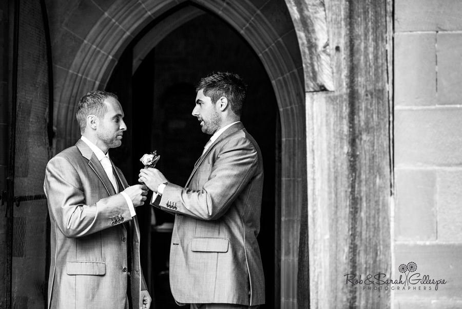 Best Man helps groom with flower
