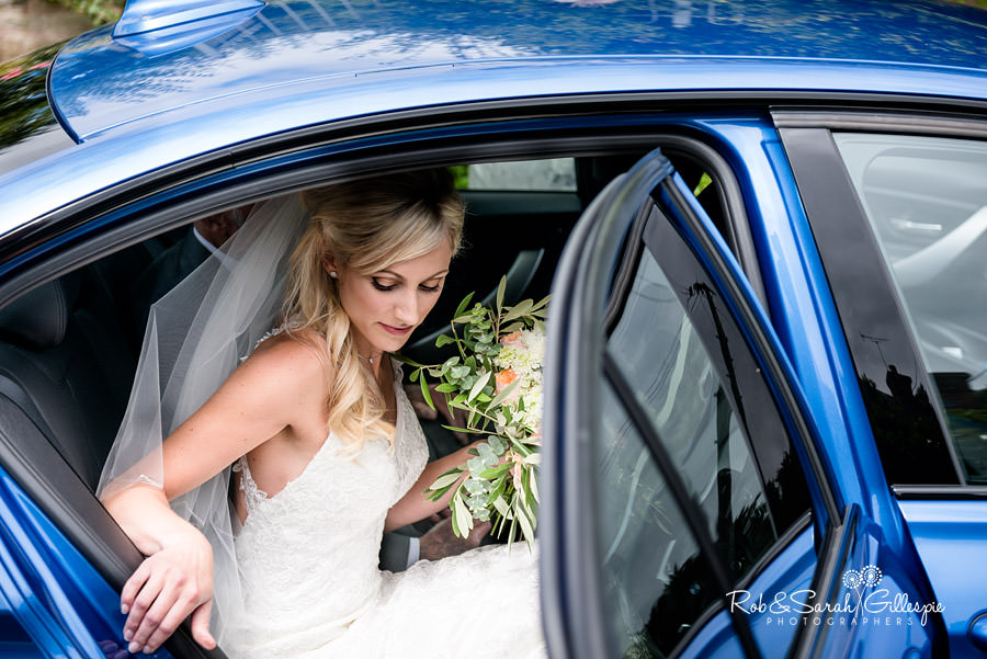 Bride arrives in car at St Peters Diddlebury for wedding