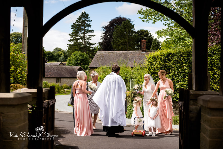 Bride and bridesmaids chat with vicar prior to church ceremony in Diddlebury Shropshire