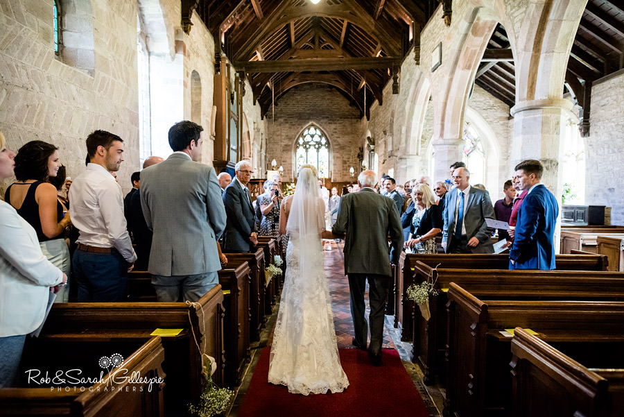 Bride walks up aisle at St Peters wedding in Diddlebury