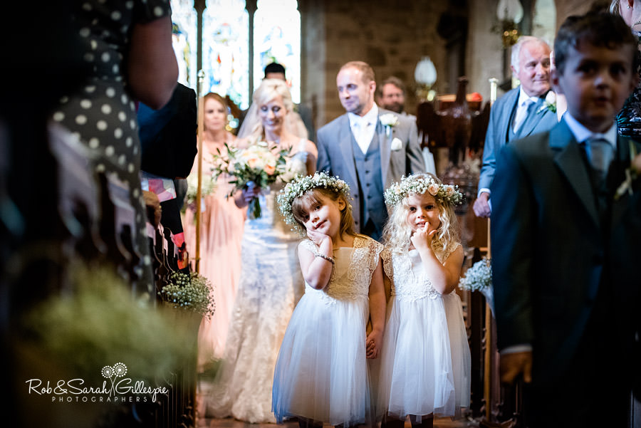 Flower girls pose for camera at end of wedding in St Peters Church Diddlebury