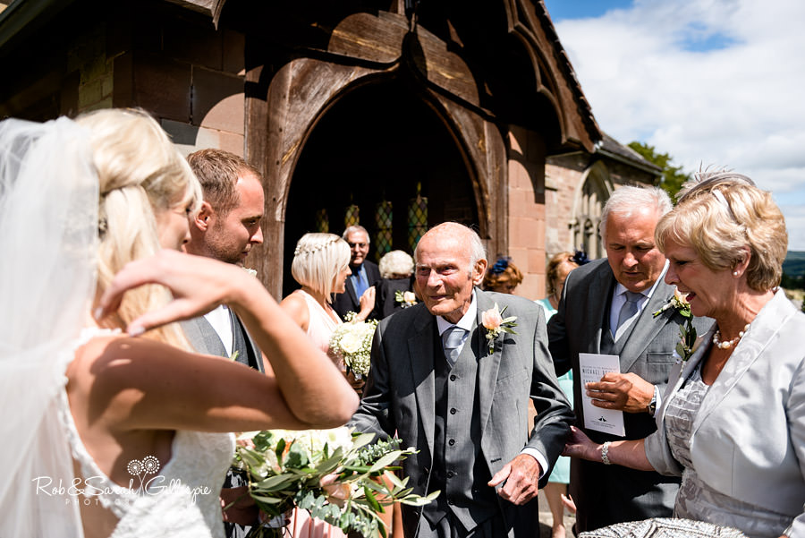 Guests congratulate bride and groom at wedding in Diddlebury