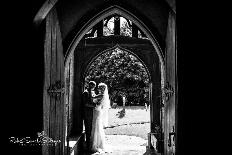 Bride and groom in church doorway at St Peters Diddlebury