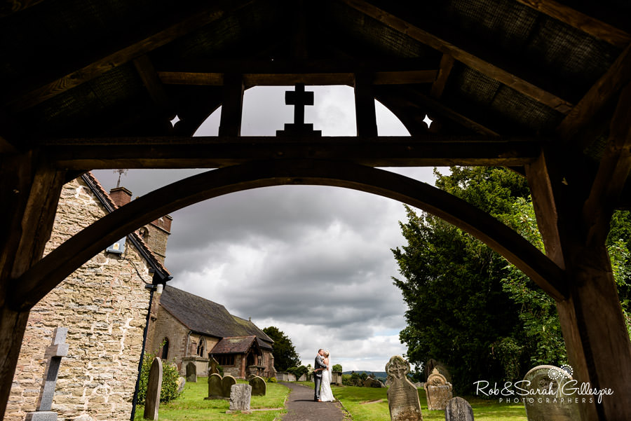 Bride and groom kiss in churchyard with lychgate arch in foreground