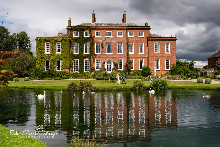 Bride and groom walk together in front of Delbury Hall with lake and swans in foreground