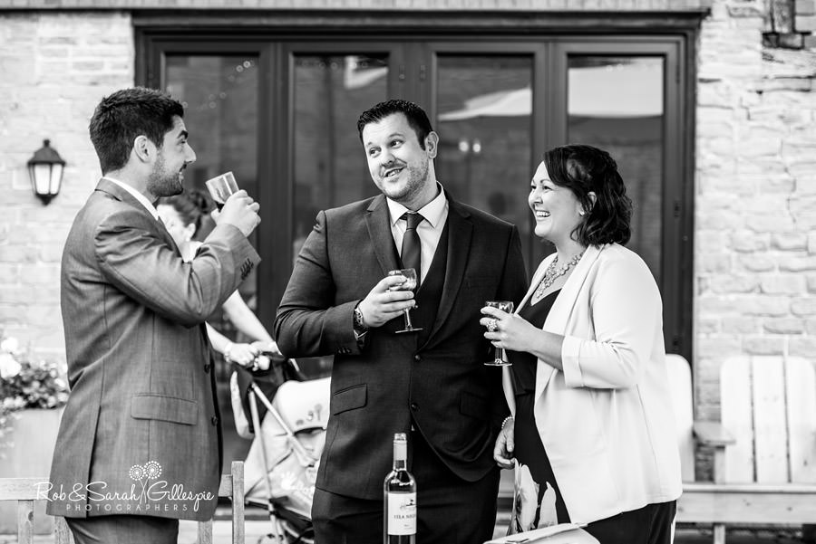 Wedding guests relax with drinks at Delbury Hall